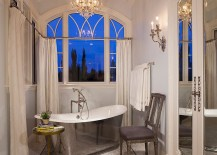 Narrow victorian bathroom with stainless steel bathtub, chair and a sleek side table