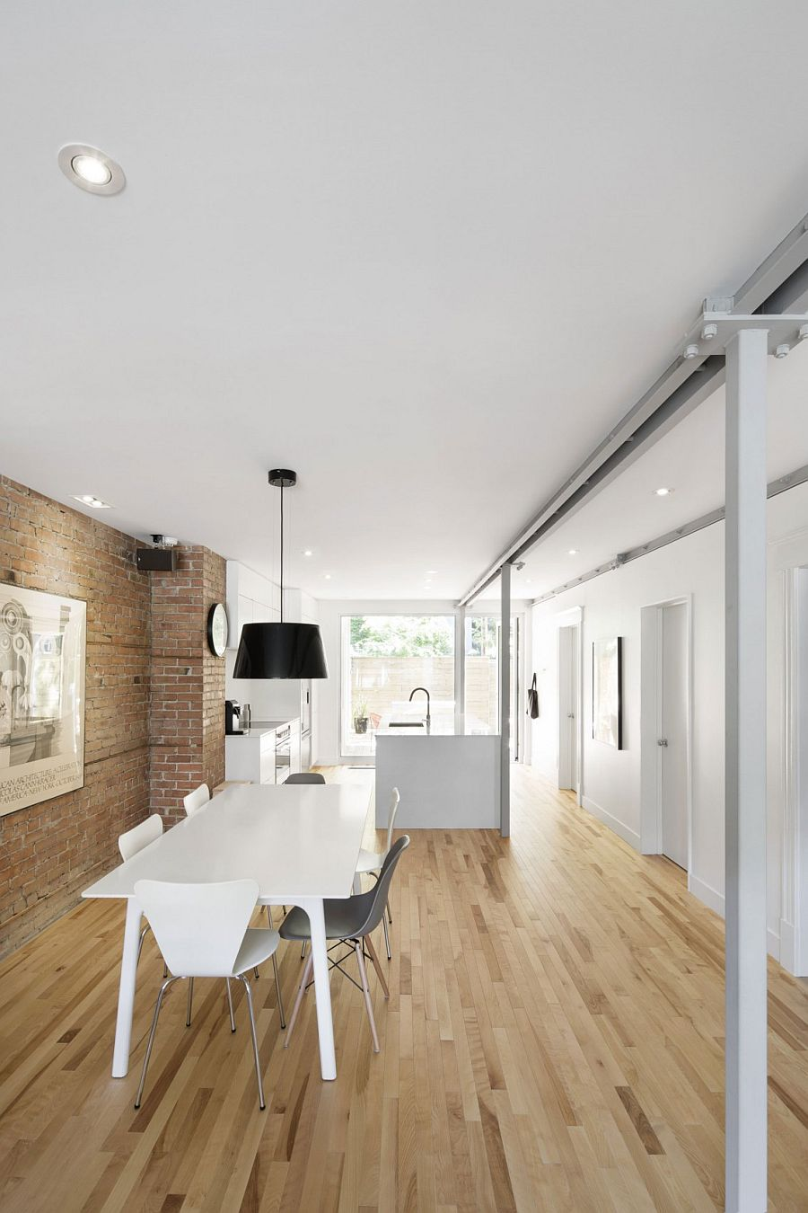 Natural birch flooring and exposed brick wall give the interior a cozy vibe