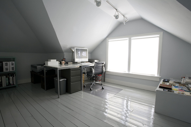 Office desk next to a huge attic window
