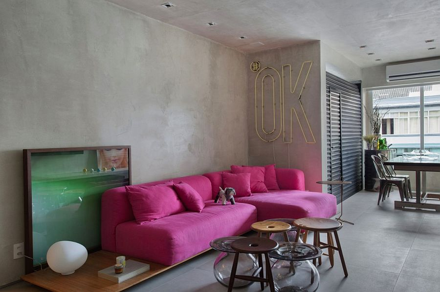 PInk sofa adds color to an otherwise neutral apartment with concrete walls