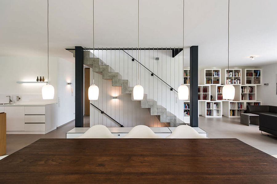 Pendant lights above the dining table complement the design of the staircase in the backdrop