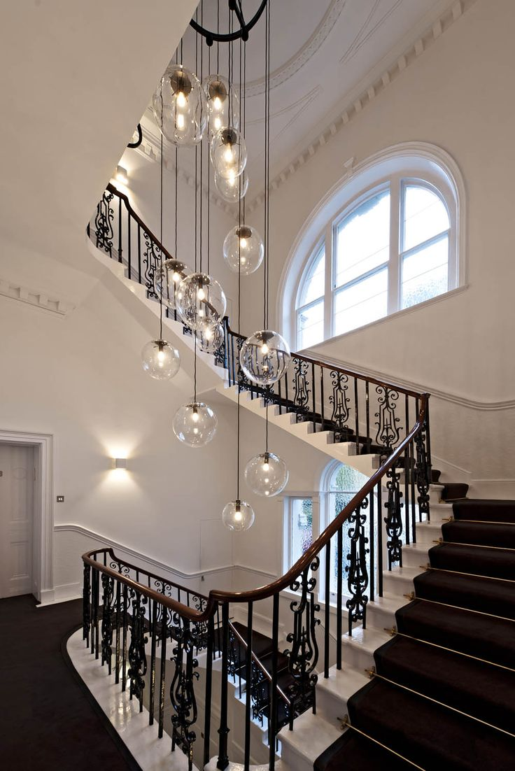 Plain glass pendant lighting hanging over a staircase