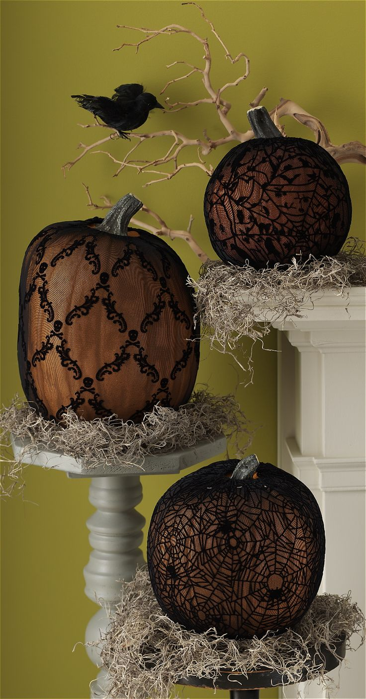 Pumpkins with black lace displayed on platforms