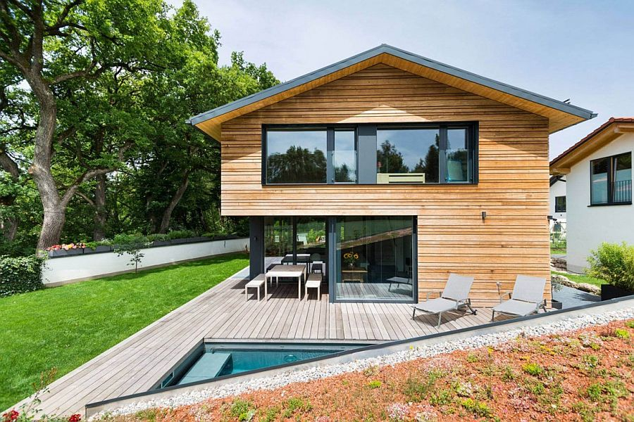 Relaxing deck and pool area of the modern house in Bavaria Home in Oberhaching: Modern Minimalism Encased in Warmth of Wood