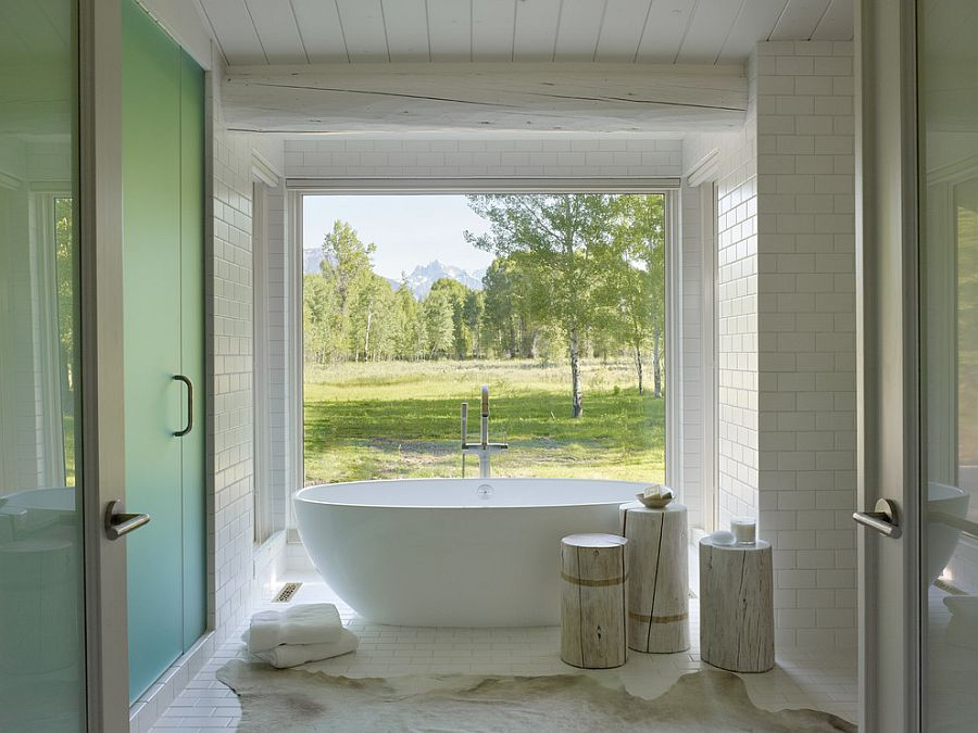 Rustic bathroom with large window connecting it with the outdoors [Design: Carney Logan Burke Architects]