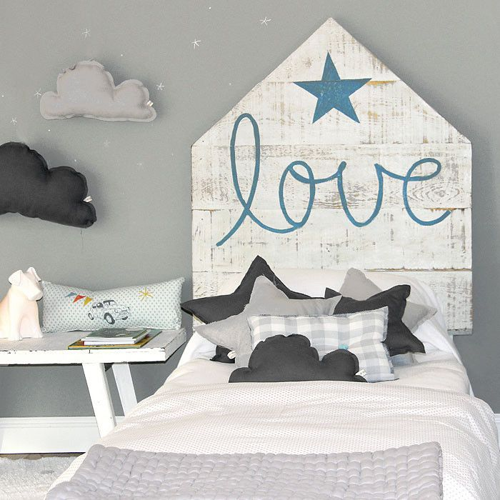 Rustic headboard and cloud-shaped pillows in a kids' bedroom