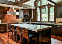 Rustic kitchen combines exposed brick and stone walls with weatherd wooden beams
