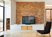 Scandinavian living room with an understated TV stand and brick wall [Design: Nic Owen Architects]