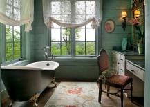 Serene Victorian bathroom with light green walls, unique rug and vintage bathtub