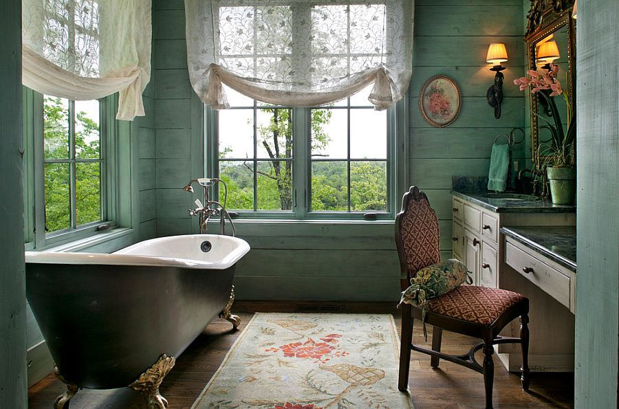 Serene Victorian bathroom with light green walls, unique rug and vintage bathtub [Design: Kathryn Long]