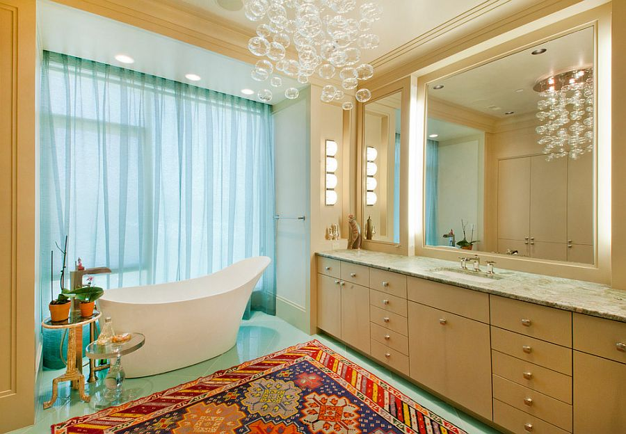 Side tables bring contrasting textures to the glorious bathroom with cascading chandelier