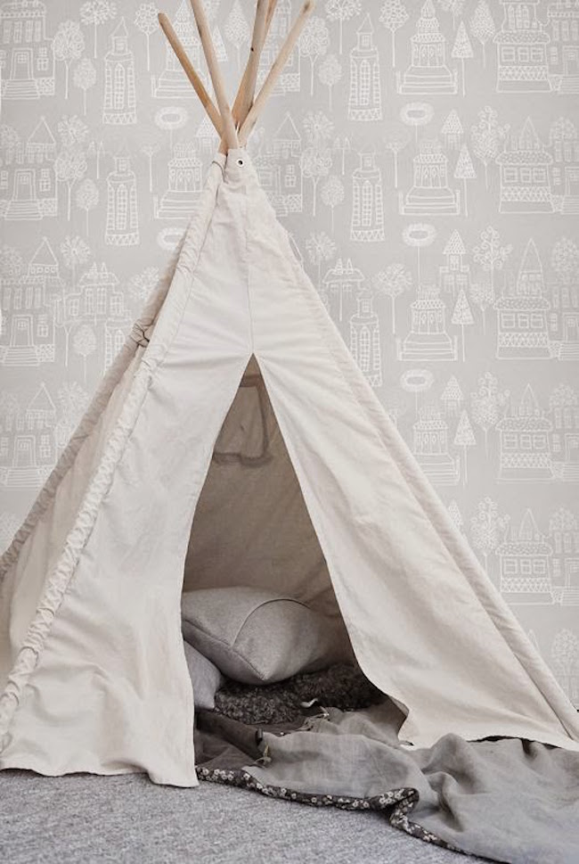 Simple white teepee with gray pillows and blankets