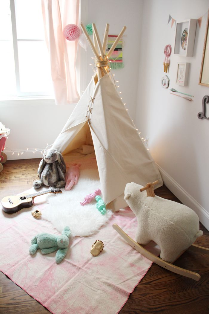 Simple white teepee with lots of toys nearby to play with