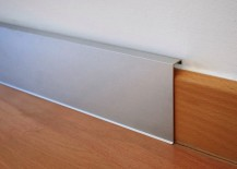 Sleek aluminum baseboard beautifully offsets wood flooring
