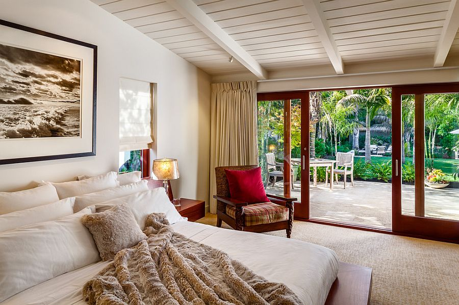 Sliding glass doors connect the bedroom with the greenery outside