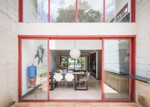 Sliding glass doors with bright red metallic frames for the concrete Brazilian home