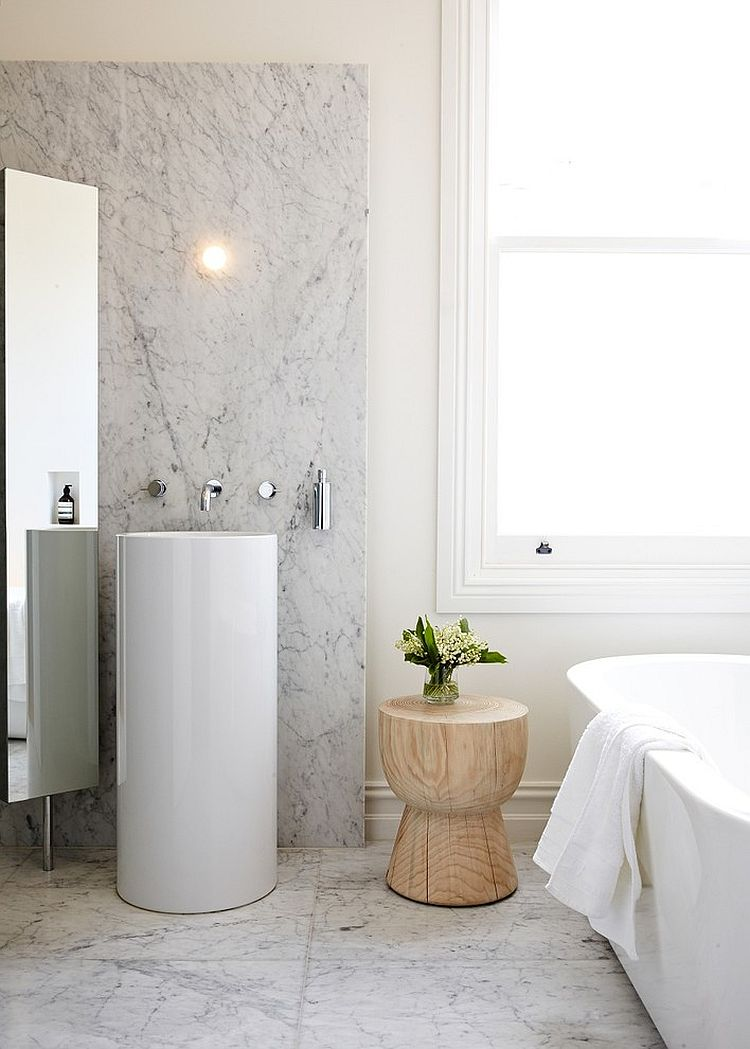 Small side table with woodsy beauty adds textural contrast to the contemporary bathroom