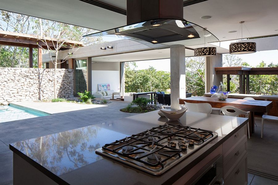 Smart outdoor kitchen and dining next to the pool deck