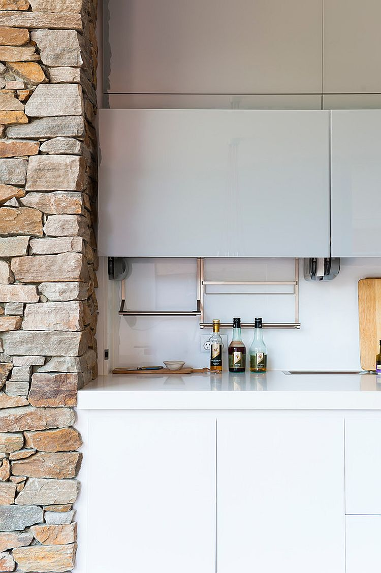 Stone fireplace interacts with glass white shelves of the kitchen