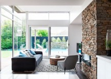 Stone wall fireplace becomes a part of both the living area and the kitchen visually