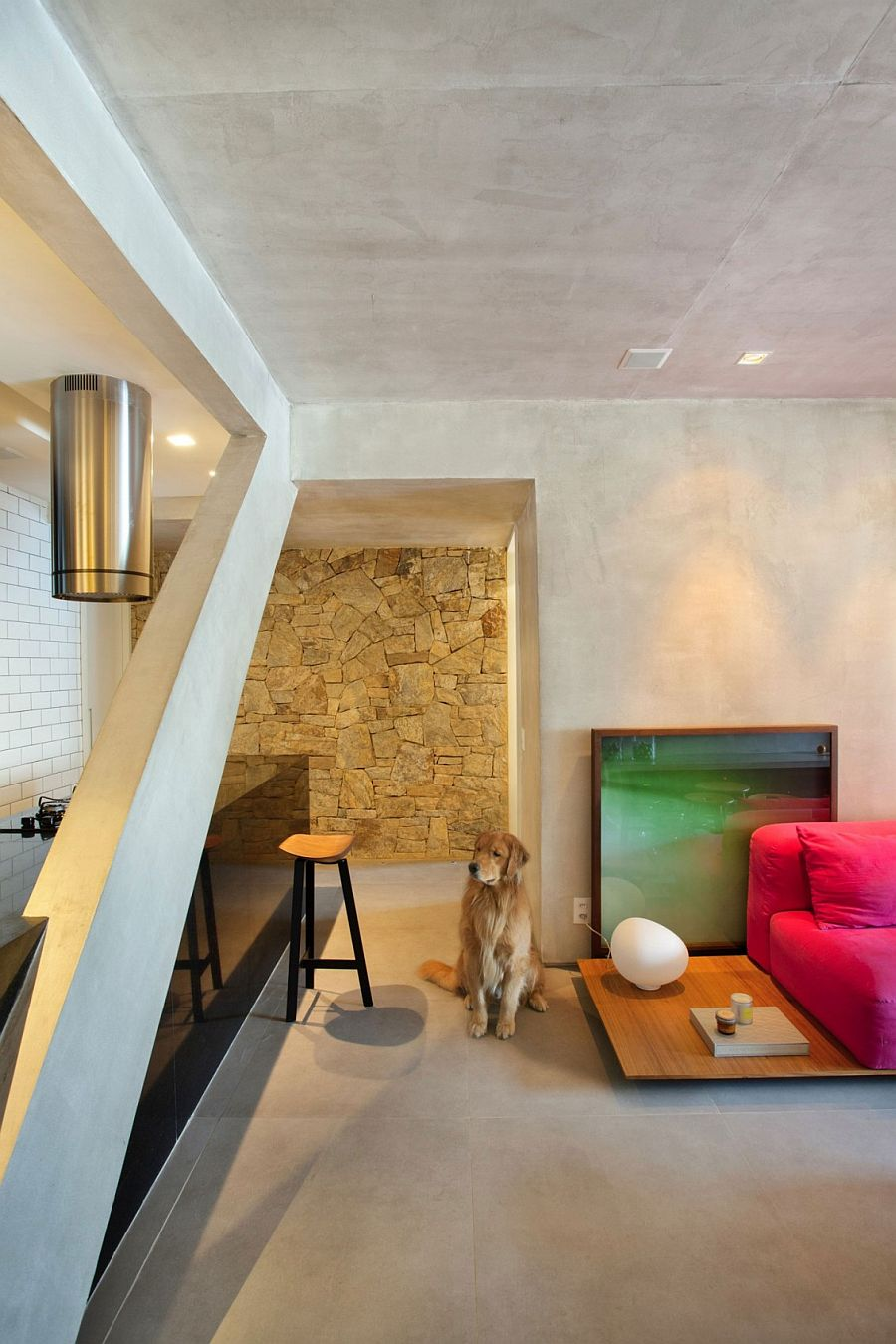 Stone wall in the kitchen adds a contrasting texture to the concrete interior
