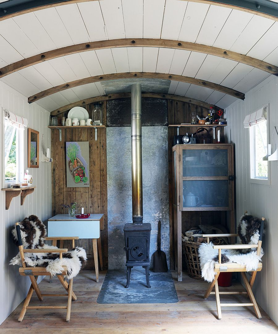 Tiny living room of refurbished railway wagon home [Design: Ryland Peters & Small - CICO Books]