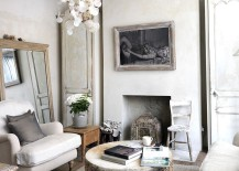 Tree trunk coffee and antique mirror epitomize the shabby chic style of the room
