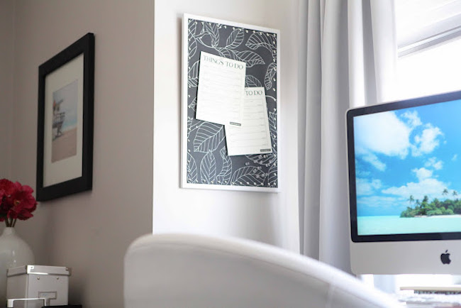 Tropical black and white fabric covering a cork board
