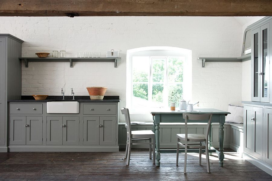 Unassuming kitchen with gray cabinets and a whitewashed brick wall