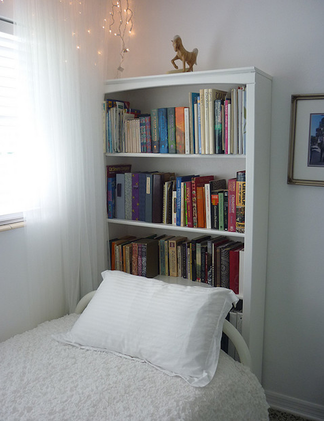 Use a bookshelf as a headboard for small rooms