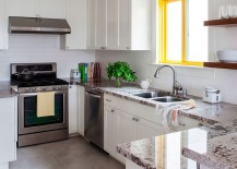 WIndow frame adds a bright spark of yellow to the white kitchen with stone countertops