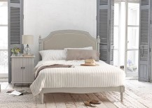 Weathered look of the flooring, shutters in gray and vintage bed usher in the shabby chic style