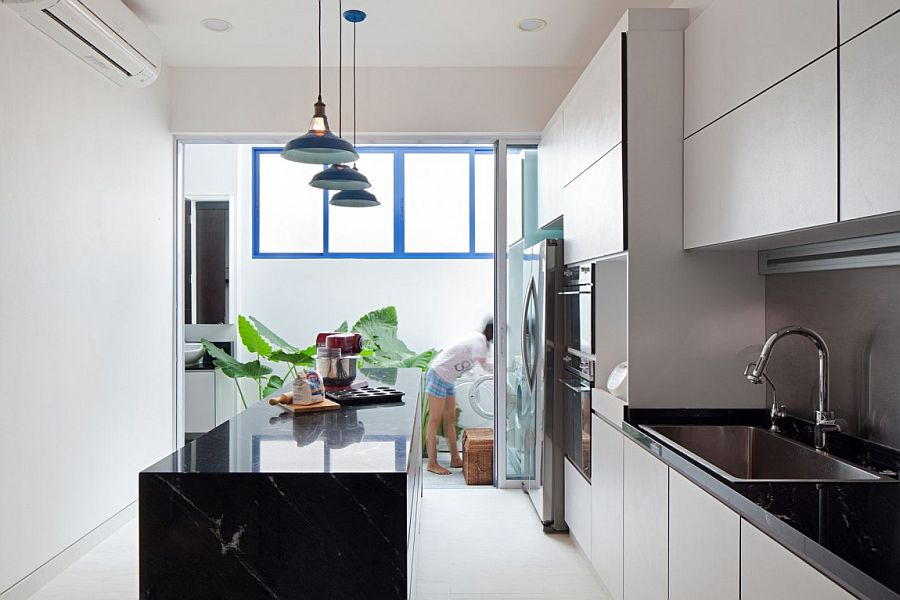 White and bright modern kitchen with dark central island and worktops in stone