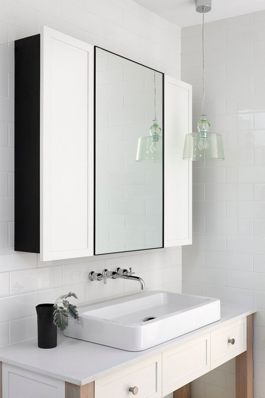White vanity and medicine cabinet of the becah style bathroom with a hint of black
