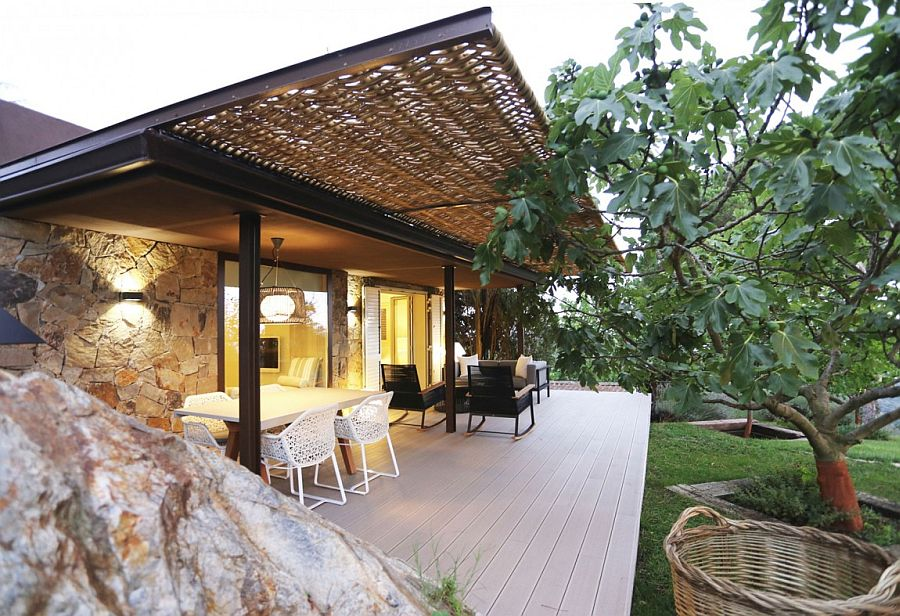 Wicker and iron pergola expands the deck space and creates a wonderful outdoor activity zone