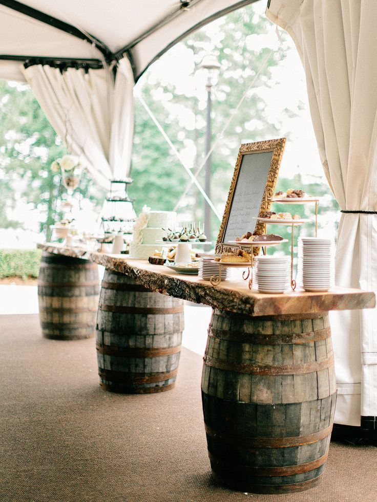 Wine barrels used to hold up the dessert table at a wedding