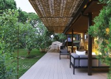 Wooden deck, wicker and iron pergola extend the living area into the lush green garden