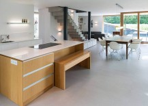 Wooden kitchen island with a stone worktop and a wooden becnh for breakfast bar