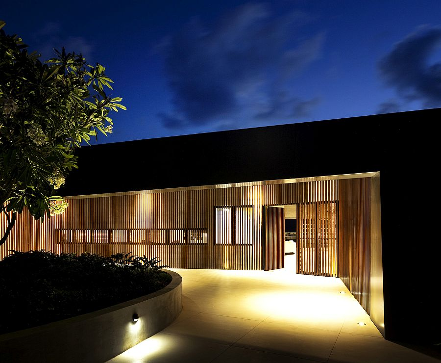 Wooden slats and brilliant lighting create a private entrance to the luxurious home