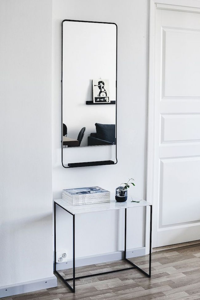 A Scandinavian entryway with striking charcoal tones for the mirror and table