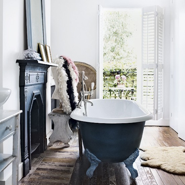 A fireplace and matching clawfoot tub in a bathroom with a balcony