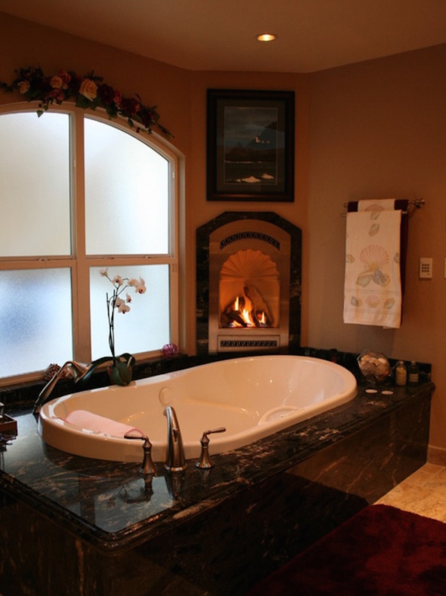 A luxurious tub with a small nearby fireplace