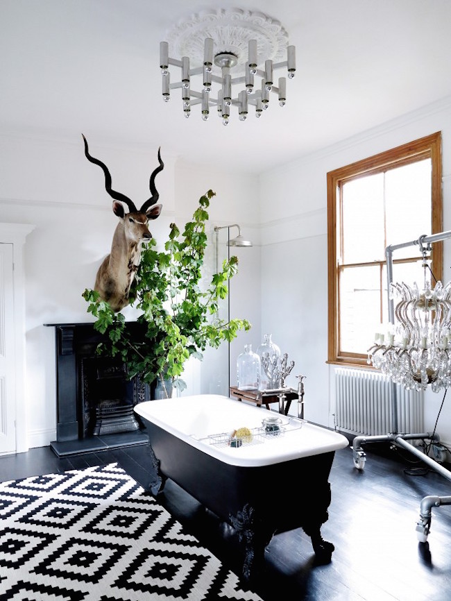 An eclectic bathroom with a gorgeous black clawfoot tub