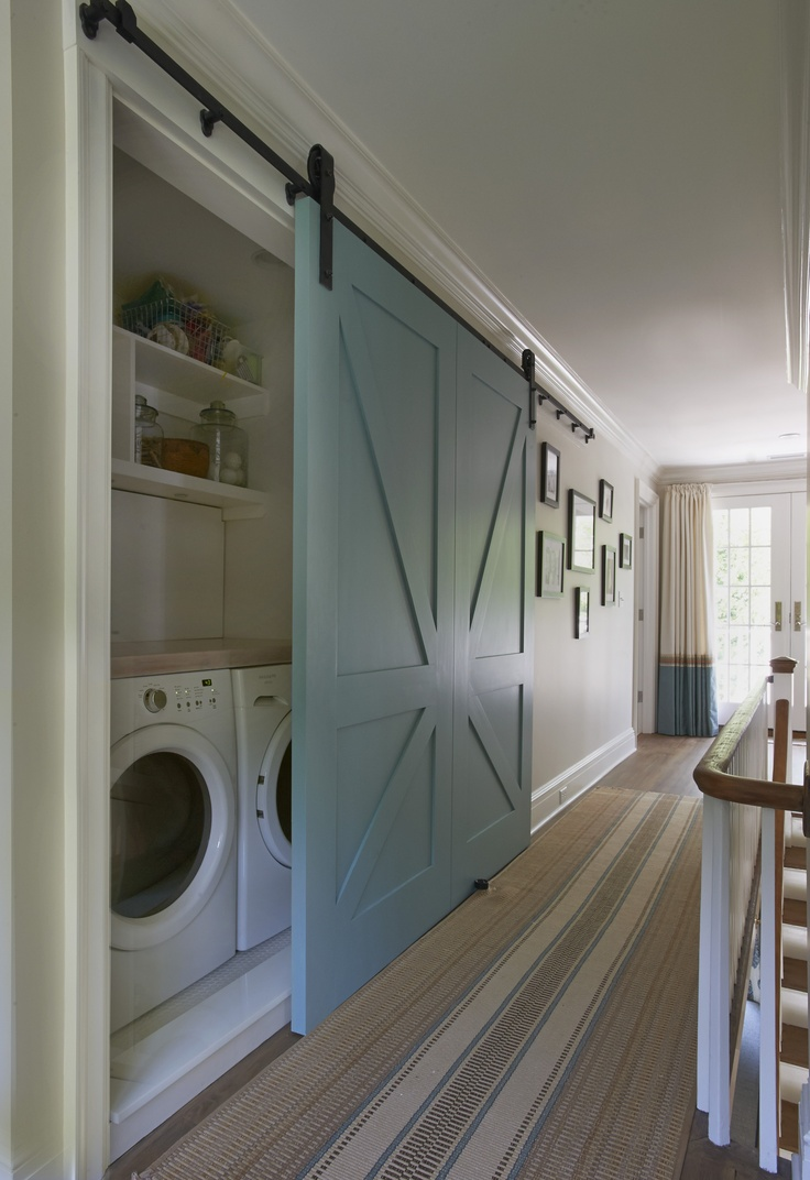Beautiful blue barn door that hides a washer and dryer