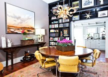 Black bookshelves separate the eclectic dining room from the kitchen