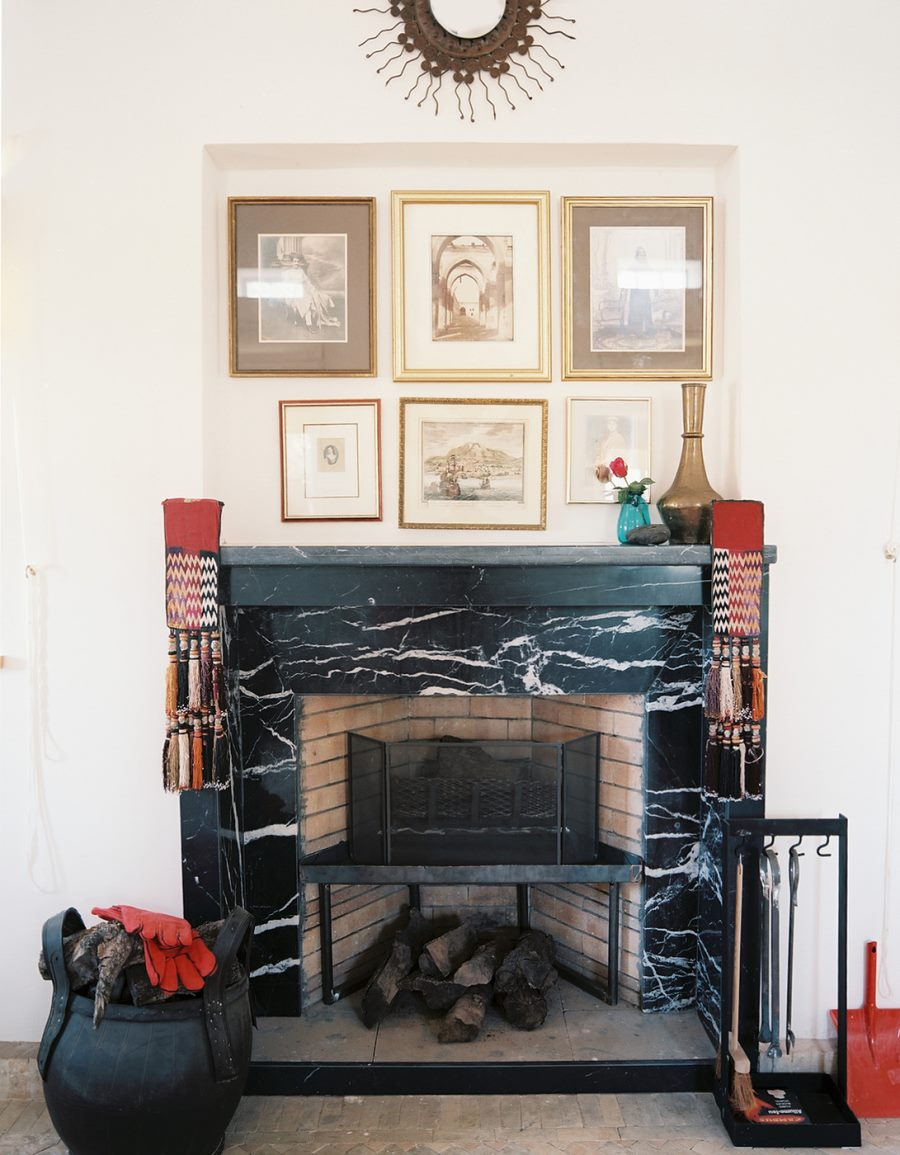 Black marble fireplace under a wall art display