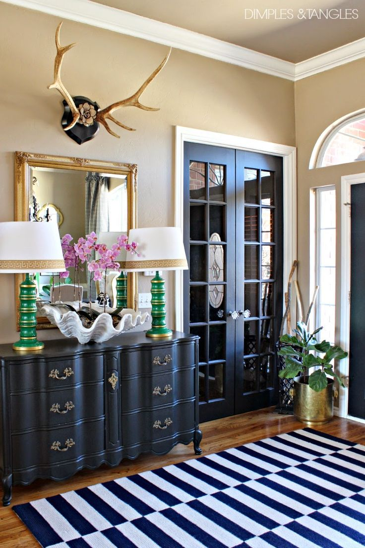 Bold and eclectic entryway with a gold framed mirror and antler decor above it