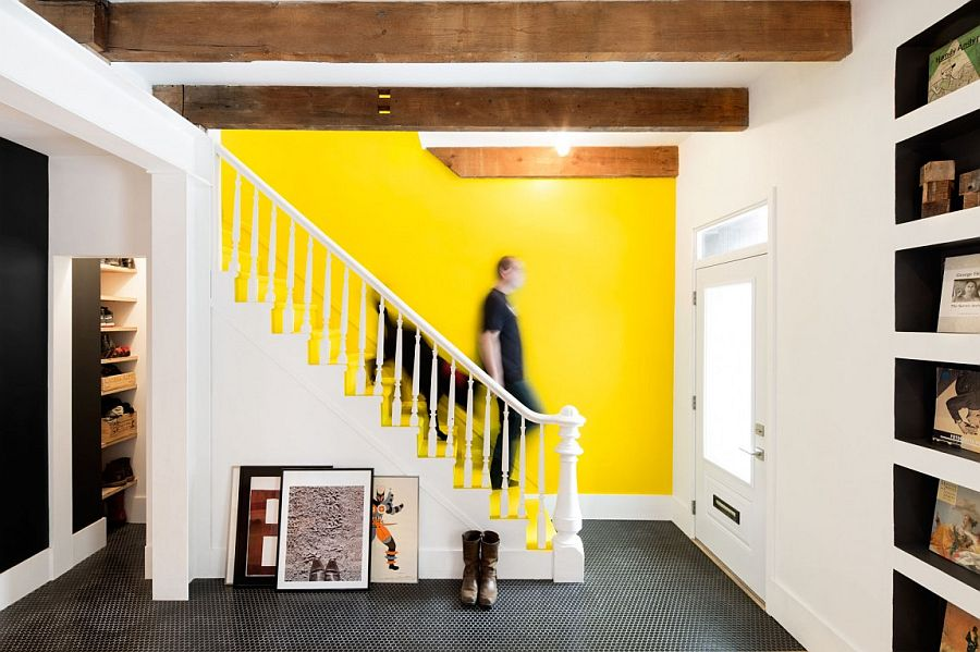Bright accent wall in yellow stands out in the black and white interior of the Quebec home Tasteful Fusion: Vivacious Remodeling of 1880s Montreal Row House
