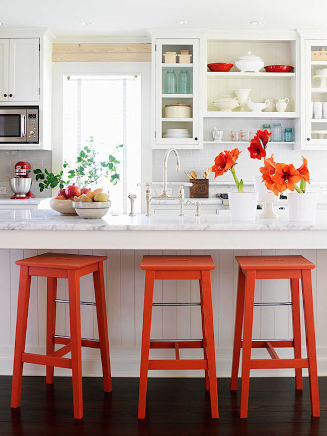 View in gallery Bright orange bar stools and accents in a white kitchen