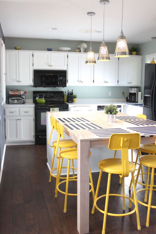 Bright yellow bar stools in a kitchen with small touches of green